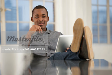 Male office worker sitting at desk with feet up Stock Photo - Premium Royalty-Free, Image code: 649-06812625