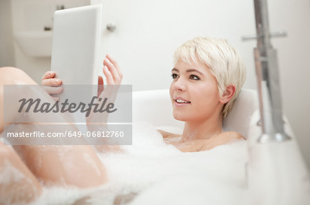 Woman using digital tablet in bubble bath Stock Photo - Premium Royalty-Free, Image code: 649-06812760