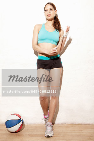 Young woman wrapping bandage on wrist Stock Photo - Premium Royalty-Free, Image code: 649-06812818