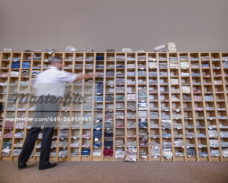 Man selecting fabric samples from shelving unit Stock Photo - Premium Royalty-Free, Image code: 649-06812953