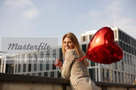 Woman with red heart-shaped balloon Stock Photo - Premium Royalty-Free, Image code: 649-06813029