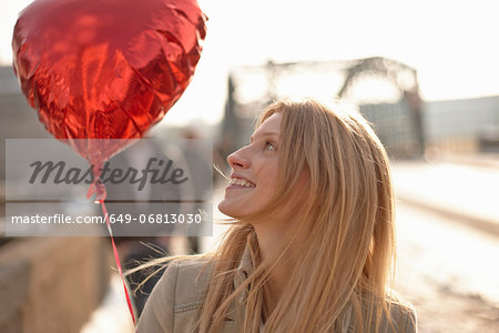 Woman with red heart-shaped balloon Stock Photo - Premium Royalty-Free, Image code: 649-06813030