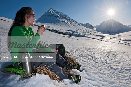 Mature woman sitting with a hot drink in snowy mountains, Skidadalur, Dalvik, Iceland Stock Photo - Premium Royalty-Free, Image code: 649-06829446