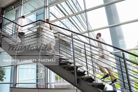 Doctors rushing up hospital staircase, blurred motion Stock Photo - Premium Royalty-Free, Image code: 649-06829492