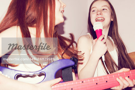 Two girls playing guitar and singing into microphone in bedroom Stock Photo - Premium Royalty-Free, Image code: 649-06829589