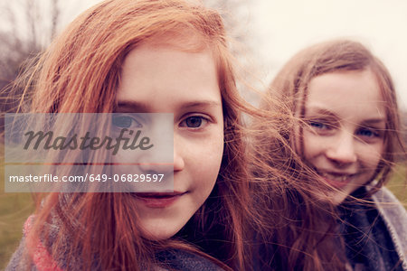 Portrait of girls wrapped in a blanket outdoors, smiling Stock Photo - Premium Royalty-Free, Image code: 649-06829597