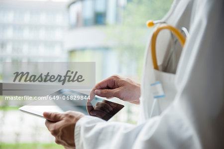 Close up of young male doctor using digital tablet Stock Photo - Premium Royalty-Free, Image code: 649-06829844
