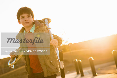 Boy in park carrying scooter Stock Photo - Premium Royalty-Free, Image code: 649-06829863