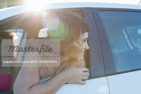 Woman looking over shoulder through car window Stock Photo - Premium Royalty-Free, Image code: 649-06829955