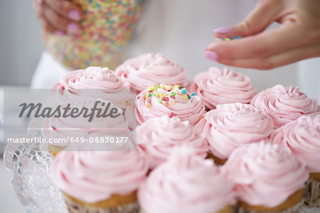 Woman decorating cupcakes with sugar sprinkles Stock Photo - Premium Royalty-Free, Image code: 649-06830177
