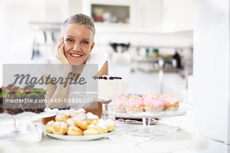 Portrait of woman with selection of hand made cakes Stock Photo - Premium Royalty-Free, Image code: 649-06830180