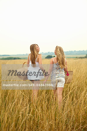 Two girls in a field with picnic baskets Stock Photo - Premium Royalty-Free, Image code: 649-06843984