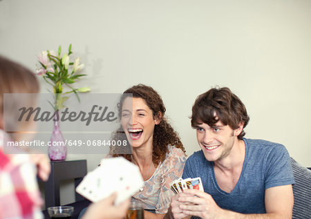Friends playing cards Stock Photo - Premium Royalty-Free, Image code: 649-06844008