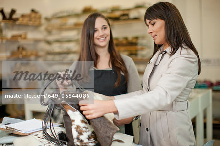 Customer and shop assistant looking at leather bag Stock Photo - Premium Royalty-Free, Image code: 649-06844086