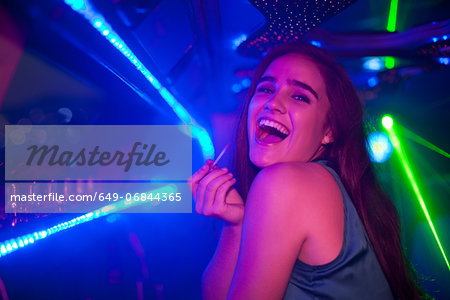 Young woman laughing at bar in nightclub Stock Photo - Premium Royalty-Free, Image code: 649-06844365