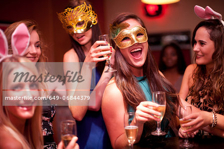 Young women with drinks wearing masks at hen party Stock Photo - Premium Royalty-Free, Image code: 649-06844379