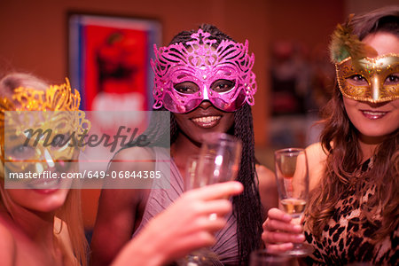 Young women wearing masquerade masks at hen party Stock Photo - Premium Royalty-Free, Image code: 649-06844385