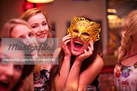Young woman wearing masquerade mask at hen party Stock Photo - Premium Royalty-Free, Image code: 649-06844386
