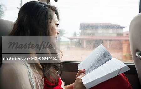Woman looking out of window on bus with book Stock Photo - Premium Royalty-Free, Image code: 649-06844461