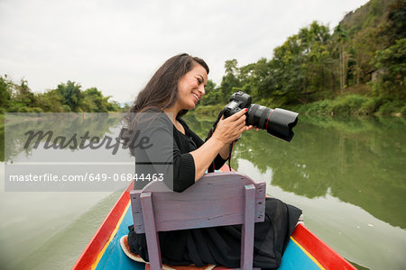 Woman with camera on boat on Nam Song River, Vang Vieng, Laos Stock Photo - Premium Royalty-Free, Image code: 649-06844463