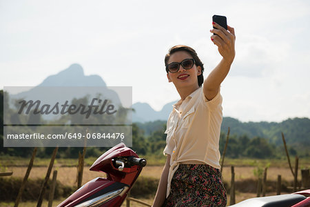 Woman photographing self on moped, Vang Vieng, Laos Stock Photo - Premium Royalty-Free, Image code: 649-06844476