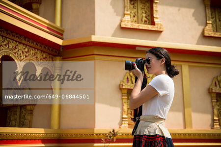 Woman taking photograph outside building, Luang Prabang, Laos Stock Photo - Premium Royalty-Free, Image code: 649-06844501