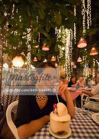 Woman drinking exotic drink in outdoor restaurant Stock Photo - Premium Royalty-Free, Image code: 649-06844510