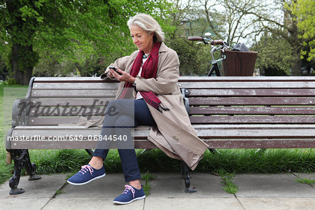 Senior woman sitting on park bench and looking at mobile phone Stock Photo - Premium Royalty-Free, Image code: 649-06844540