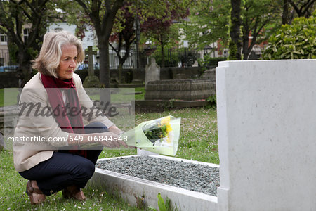 Senior woman holding flowers at grave stone Stock Photo - Premium Royalty-Free, Image code: 649-06844548