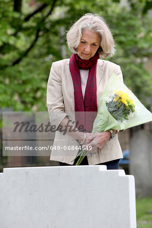 Senior woman holding flowers in graveyard Stock Photo - Premium Royalty-Free, Image code: 649-06844549