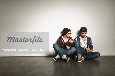 Teenage boys sitting cross legged leaning against wall listening to mp3 player Stock Photo - Premium Royalty-Free, Image code: 649-06844577