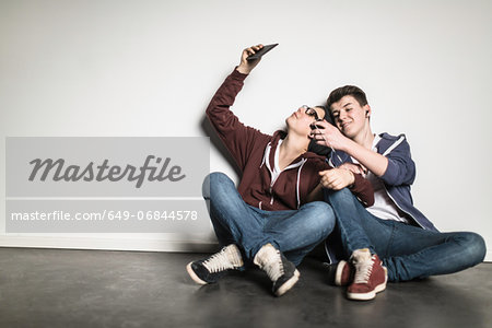 Teenage boys sitting cross legged leaning against wall using smartphones Stock Photo - Premium Royalty-Free, Image code: 649-06844578