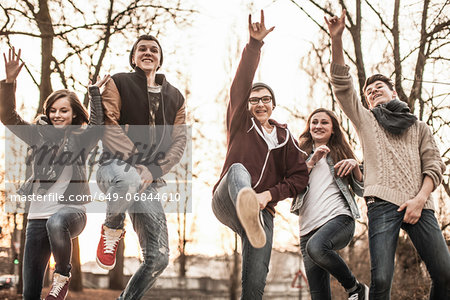 Five teenagers fooling around, jumping in park Stock Photo - Premium Royalty-Free, Image code: 649-06844610