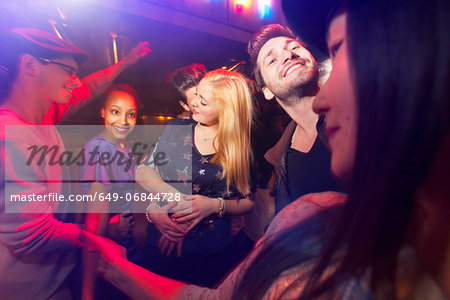 Group of people at party, man kissing woman's neck Stock Photo - Premium Royalty-Free, Image code: 649-06844728