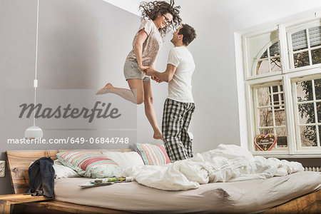 Mid adult couple wearing pyjamas jumping on bed Stock Photo - Premium Royalty-Free, Image code: 649-06844748