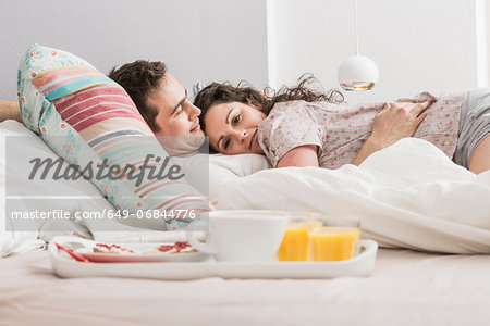 Mid adult couple lying in bed, breakfast on tray, hugging Stock Photo - Premium Royalty-Free, Image code: 649-06844776