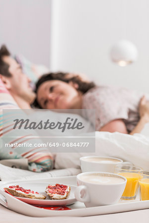 Mid adult couple lying in bed, breakfast on tray, hugging Stock Photo - Premium Royalty-Free, Image code: 649-06844777