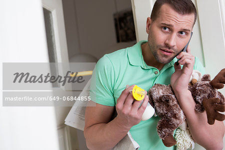 Mid adult man holding cuddly toy and baby's pacifier Stock Photo - Premium Royalty-Free, Image code: 649-06844855