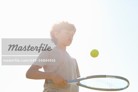 Boy bouncing ball on tennis racket Stock Photo - Premium Royalty-Free, Image code: 649-06844916