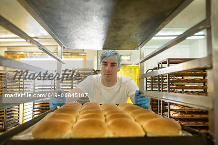 Baker organising trays of freshly baked bread Stock Photo - Premium Royalty-Free, Image code: 649-06845107