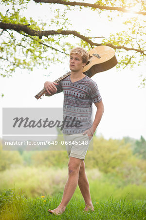 Young man walking through field with guitar Stock Photo - Premium Royalty-Free, Image code: 649-06845148