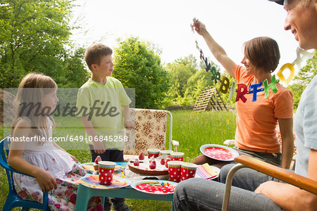 Family with two children celebrating birthday outdoors Stock Photo - Premium Royalty-Free, Image code: 649-06845258