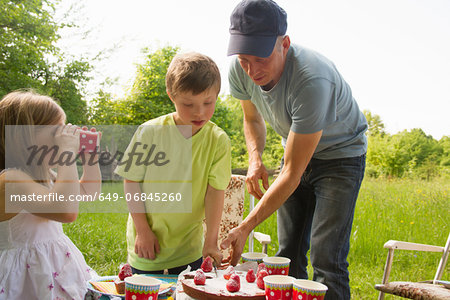 Father with two children cutting birthday cake outdoors Stock Photo - Premium Royalty-Free, Image code: 649-06845260