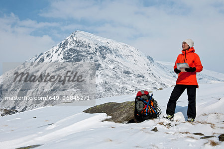 Female climber with map on snow covered mountain, Carneddau, Snowdonia Stock Photo - Premium Royalty-Free, Image code: 649-06845271