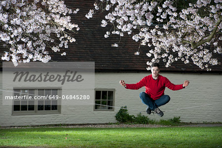 Portrait of young man meditating on a slackline Stock Photo - Premium Royalty-Free, Image code: 649-06845280