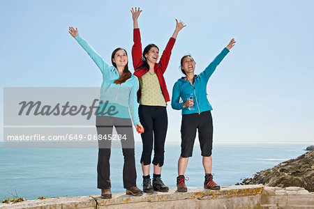 Three female friends waving from wall at coast Stock Photo - Premium Royalty-Free, Image code: 649-06845284