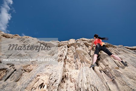 Female rock climber nearing cliff top Stock Photo - Premium Royalty-Free, Image code: 649-06845292