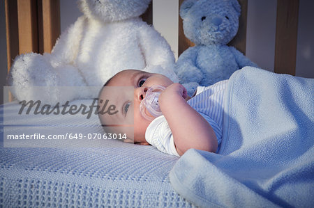 Baby boy and teddy bears in crib at night Stock Photo - Premium Royalty-Free, Image code: 649-07063014
