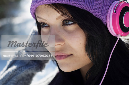 Close up portrait of young female listening to headphones Stock Photo - Premium Royalty-Free, Image code: 649-07063056