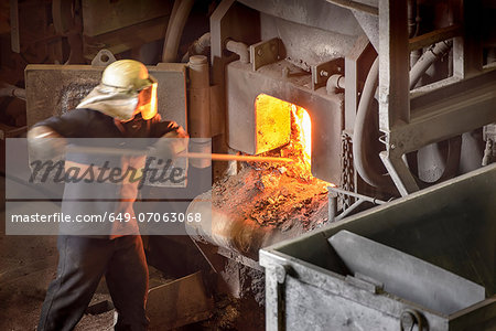 Steel worker poking furnace in steel foundry Stock Photo - Premium Royalty-Free, Image code: 649-07063068